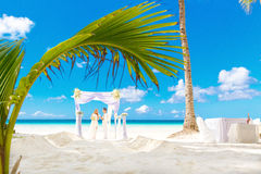 Wedding ceremony on a tropical beach in white. Happy groom and b Stock Images
