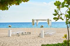 Beautiful beach wedding venue setting with flowers decoration, panoramic ocean view. Wedding ceremony venue setup for small size on the beach, white sand with Stock Photo