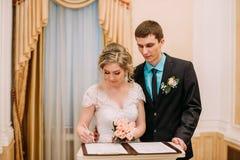 Wedding ceremony. Wedding couple leaving their signatures. Happy couple. Wedding photo shoot in the white studio with wedding decor kisses, hugs. Having fun Royalty Free Stock Image
