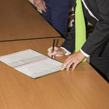 Wedding ceremony. Wedding groom leaving his signature. Groom or business man leaving his signature, in the office Royalty Free Stock Image