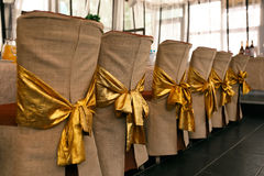 Wedding chair decoration. Beige covers and golden bowings of chair backs. Wedding chair decoration. Beige covers and gold bows on the backs of chairs. Horizontal Stock Photos