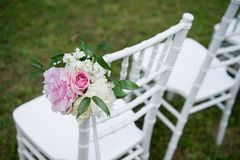 Decorated wedding chair. Formal, marriage. Wedding chair. Outdoor. Formal, marriage. White and pink peonies with green elements and some roses Royalty Free Stock Image
