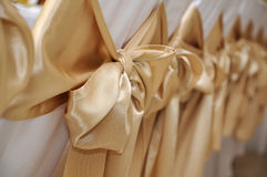 Wedding chairs. White wedding chairs decorated with golden bows Royalty Free Stock Images