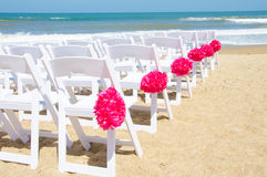 Wedding chairs on the beach. White chairs with pink floral decorations have been set up for a wedding to be held at the beach Stock Photos