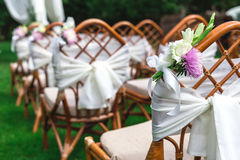 Wedding chairs decorated with flowers. Close up. Royalty Free Stock Photography