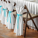 Wedding chairs, decorated with white fabric and blue ribb Stock Images