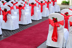 Wedding chairs. Wedding chairs decorated in white, red ribbons and red rose and pave way with carpet Royalty Free Stock Photo