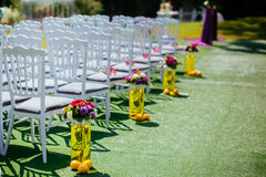 Wedding chairs on each side of archway. Wedding white wooden chairs on each side of archway, with vases and lemons near them Stock Photos