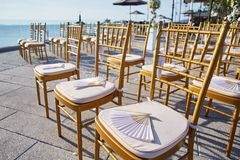 Wedding chairs gold, chinese fan souvenirs, Cones of rose petals. Sea background After ceremony Stock Photography
