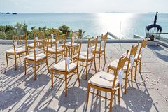 Wedding chairs gold, chinese fan souvenirs, Cones of rose petals. Sea background After ceremony Stock Image