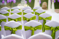Wedding chairs. The green ribbon decoration on wedding chair cover Stock Photos