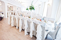 Wedding chairs with white ribbons at reception. Royalty Free Stock Photo