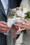 Wedding champagne. In hands of the groom and the bride against a bouquet Royalty Free Stock Photo