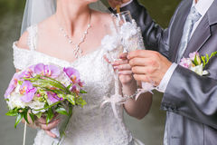 Wedding glasses in hands of groom and bride Royalty Free Stock Images