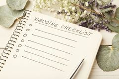 Wedding checklist and cute flowers. Wedding checklist with copy space and cute flowers on the white desktop. Marriage planner concept, copy space Royalty Free Stock Images