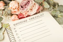 Wedding checklist and rose bouquet. Wedding checklist with copy space and rose bouquet on the white desktop. Marriage planner concept, copy space Royalty Free Stock Photography