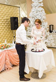 Wedding in Christmas. Bride and groom eating cake at reception Royalty Free Stock Photos
