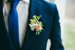 Close up image of beautiful boutonniere on the groom`s jacket. Soft focus on boutonniere. Artwork Stock Photo