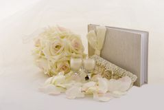 Wedding Collection. Garter, champagne glass candles, guest book, fabric flower bouquet with a veil as a background Royalty Free Stock Photos