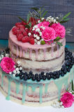 Wedding color drip cake with roses, blueberries and  raspberries Stock Photo