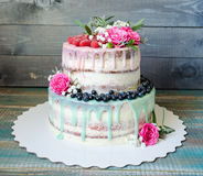 Wedding color drip cake with roses, blueberries and  raspberries Royalty Free Stock Image