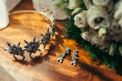 Wedding composition consisting of silver long earrings with diamonds, hair hoop with iron flowers and bouquet of white. Roses on the floor royalty free stock photography