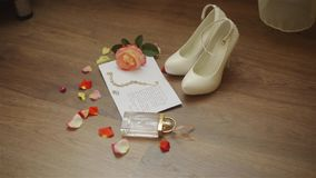 Wedding composition. Morning of the bride. Close up of wedding white shoes on high heels. Rings, rose petals and wedding stock video footage