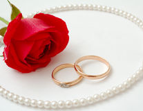 Wedding concept. Red rose with wedding rings and necklace Stock Image