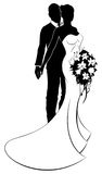 Wedding Concept Bride and Groom Silhouette. Wedding concept of bride and groom couple in silhouette with the bride in a white bridal dress gown holding a floral Stock Photography