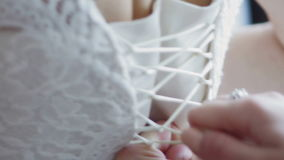 Wedding concept - bridesmaid tying bow on wedding dress. Close up stock video footage