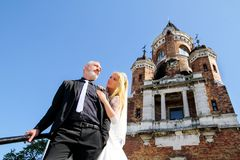 A handsome wedding couple is standing on the stairs in front of the beautiful old church. stock photo