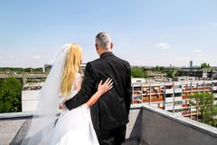 Handsome married couple standing on the roof and watch the urban city. stock images