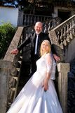 The happy handsome wedding couple are standing steps in front of house. stock photo