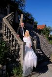 The happy handsome wedding couple are standing steps in front of house. royalty free stock image