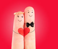 Wedding concept, newlyweds with  heart against red background Royalty Free Stock Images