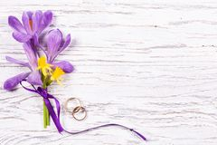 Wedding concept with spring flowers and two golden rings royalty free stock image