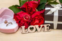 Wedding concept. text love with wedding rings, gift box and red roses. Wedding concept. text love with wedding rings, gift box and red roses Royalty Free Stock Images