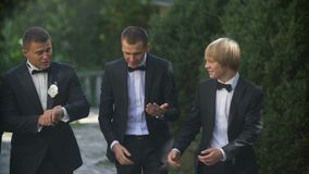 Wedding concept. The young handsome groom is happily talking with his three best man while walking along the garden.