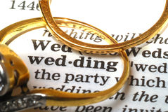Wedding with copy space. The word wedding out of a dictionary with gold rings next to it Stock Images
