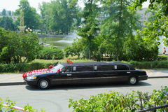 Wedding cortege. Chic black car decorated with flowers ready for the reception of a young couple Stock Photo