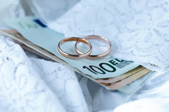 Wedding cost concept by rings and money and the bride dress in b Royalty Free Stock Photography