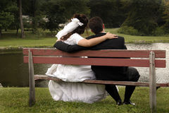 Wedding couple. A newly married couple sits with the arms around each other on bench overlooking a lake stock images