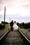 Wedding couple. Back view of a bride and groom walking down rail road tracks royalty free stock photography