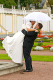 Wedding couple. Newlywed groom lifting up his wife in a surprise moment Stock Images
