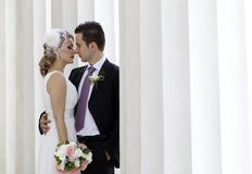 Wedding couple. Young wedding couple between columns royalty free stock photography