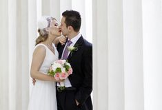 Wedding couple. Young wedding couple kissing between white columns royalty free stock photos