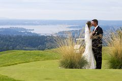 Wedding Couple. A couple kissing each other on a golf course on thier wedding day Royalty Free Stock Photography