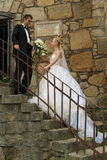 Wedding couple. On stairs; the groom is giving to his wife the bouquet Stock Image