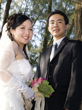 Wedding Couple-4. Wedding couple holding flower bouquet smiling in the golf course Royalty Free Stock Photos