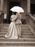 Wedding couple. A wedding couple under the umbrella in sepia color Royalty Free Stock Images